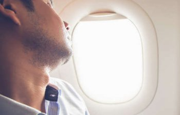 A man in a plane window seat sleeping during his flight