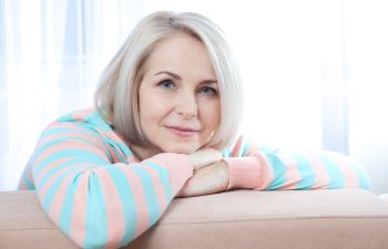 relaxed middle-aged woman a couch at her home