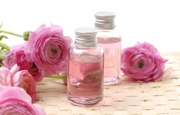 little bottles with Spa massage oils among pink flowers
