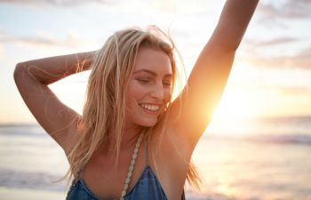 Healthy happy young woman dancing on the beach at sunset